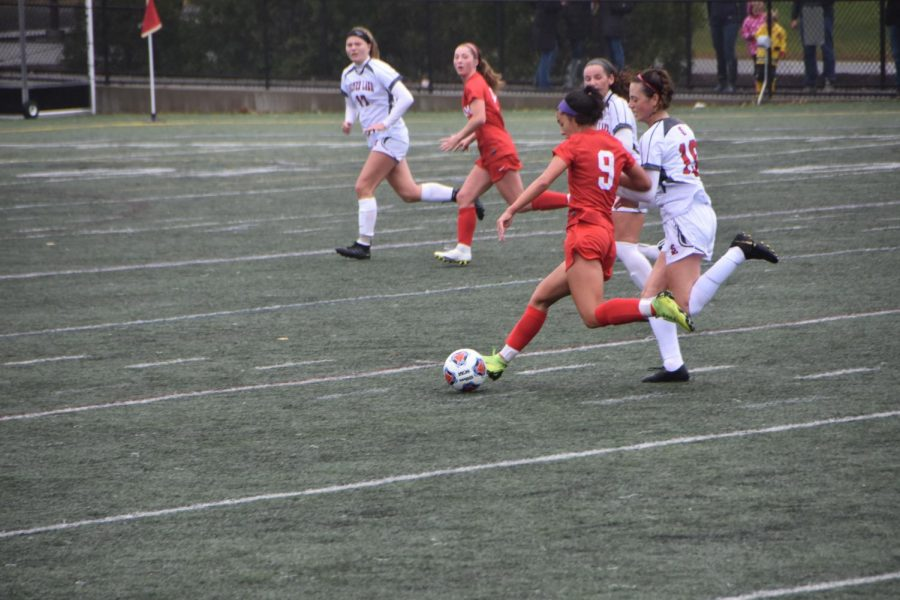 Sophomore Riley Cotter (#9) crosses the ball to senior Taylor Aymar (#8).