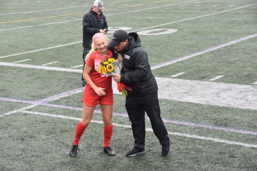 As part of the Hingham High Girls Varsity Soccer team's senior day celebration, Coach Puntiri hugs and gives flowers to senior Corinne Hanney (#20). The celebration honored seniors: Taylor Aymar (#8), Corinne Hanney (#20), Emma Hynes (#14), Captain Phoebe Murphy (#12), Captain Jess Parnell (#2), and Captain Emma Quilty (#16).