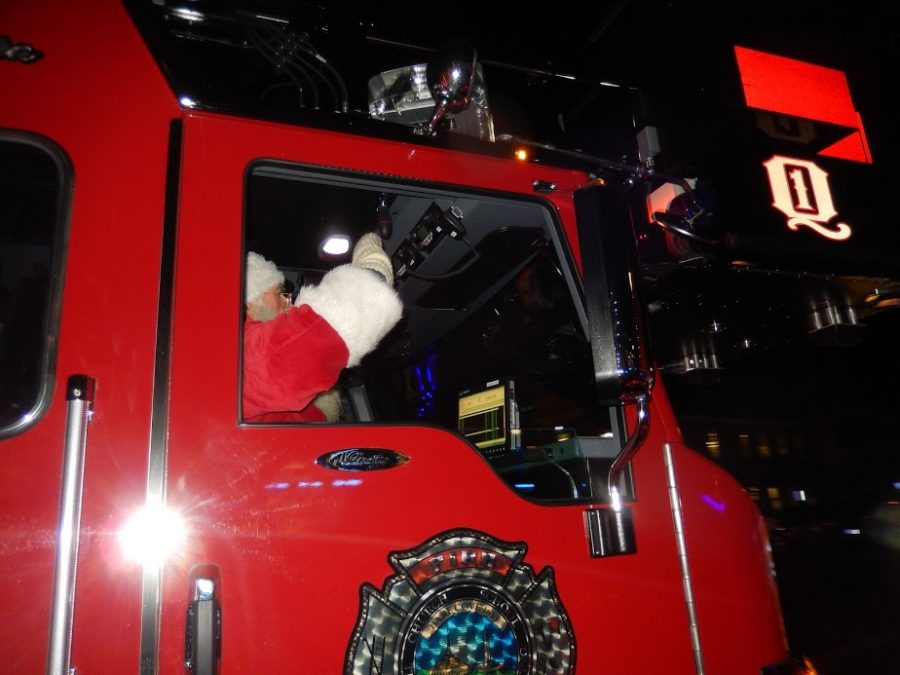 Santa rides into the square in the front seat of a fire truck.