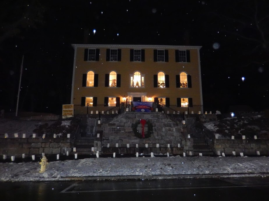 As a light snow falls, the festival of the trees is visible inside of the Old Derby Academy. It is easy to see the lanterns that surround the steps and sidewalk.