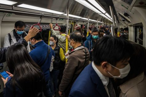 A Chinese subway filled packed to the brim with masked passengers.