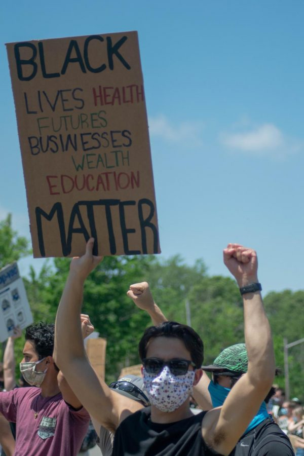 A sign that reads, Black lives, health, futures, businesses, wealth, and education matter, is held by one passionate protester.