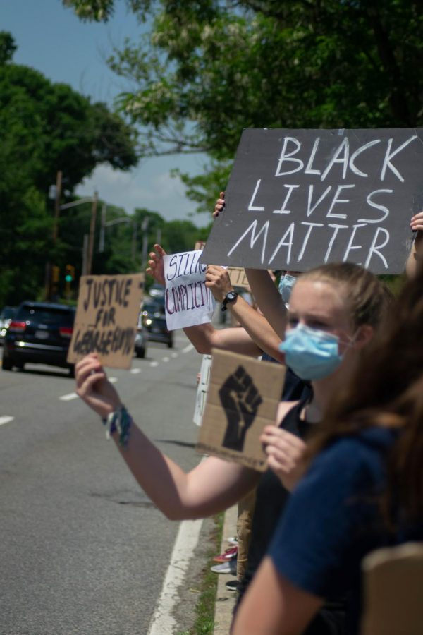 More Protesters hold up signs to declare their stance on systemic racism.