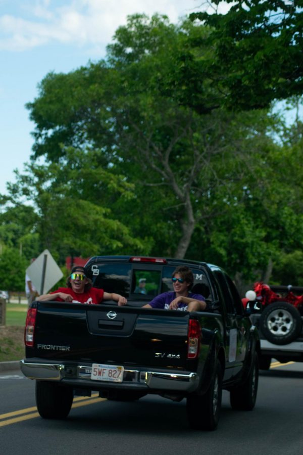 Two Seniors road in the back of a truck as the crowed cheered.