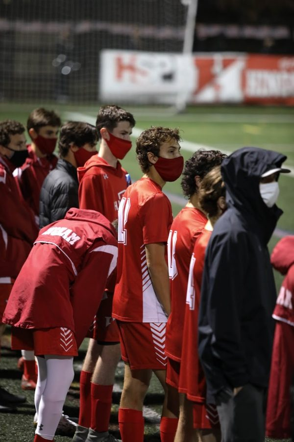 The players watch as the starting line up begins the game.