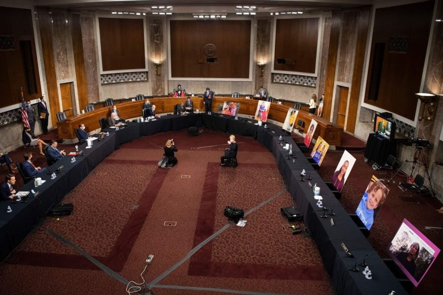 Portraits of individuals who rely on the Affordable Care Act occupy the seats of the Senate Judiciary Committee Democrats who boycotted the vote to protest the advancement of Judge Barrett's confirmation process to the Supreme Court to the Senate.