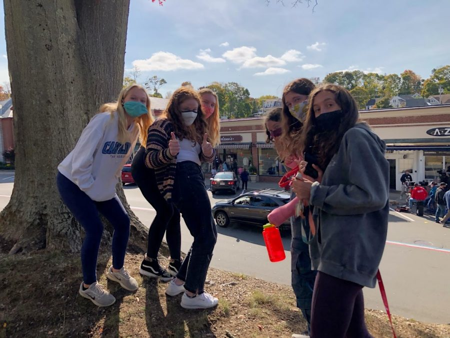 From Left: Junior Allie Briggs, Senior Mia Kourafas, Junior Sadie Burm, Senior Julia Burm, Junior Delaney Coppola, and Junior Mila Ranocha pose for a quick photo with Schitt's Creek's Annie Murphy who stands across the street in a green jacket and pink sweater.