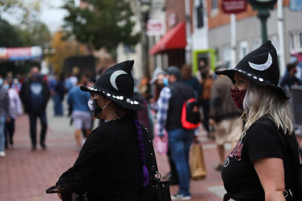 Salem, MA: October 16, 2020: Visitors wear masks as they walk along the Essex Street Pedestrian Mall in Salem, Massachusetts.