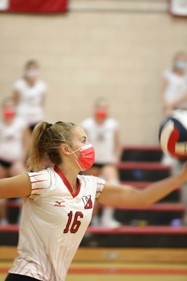 Senior captain Carly Kennedy sports her red Hingham mask as she sets up to serve the ball.