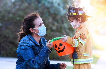A parent helps her young firefighter with his candy bag on Halloween while following COVID-19 protocol in masks.