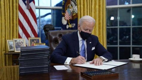 President Biden signing executive orders on his first day in office.