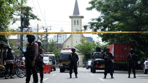 Police officers protect the Sacred Heart of Jesus Cathedral after the suicide bombing in Makassar.
