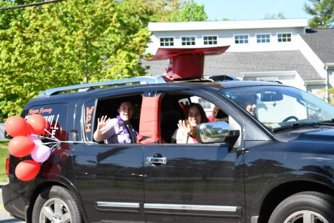 Megan Fennelly, Olivia Spielberger, and Brian Fennelly wave from their car as they drive down Main Street.