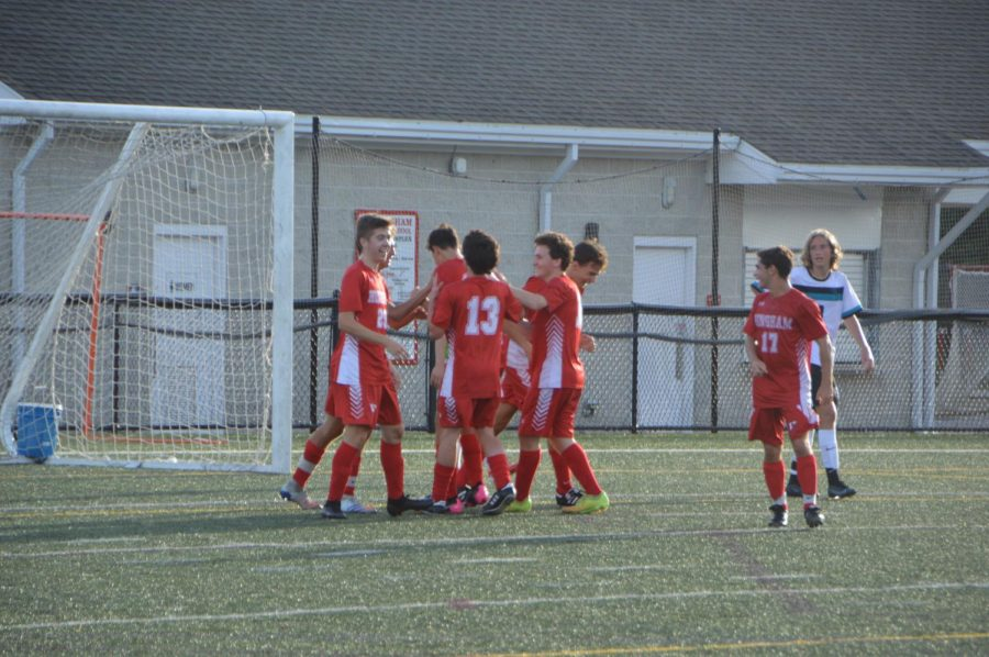 The team rushes in excitement to senior Miguel Villacieros after scoring his first goal of the season.